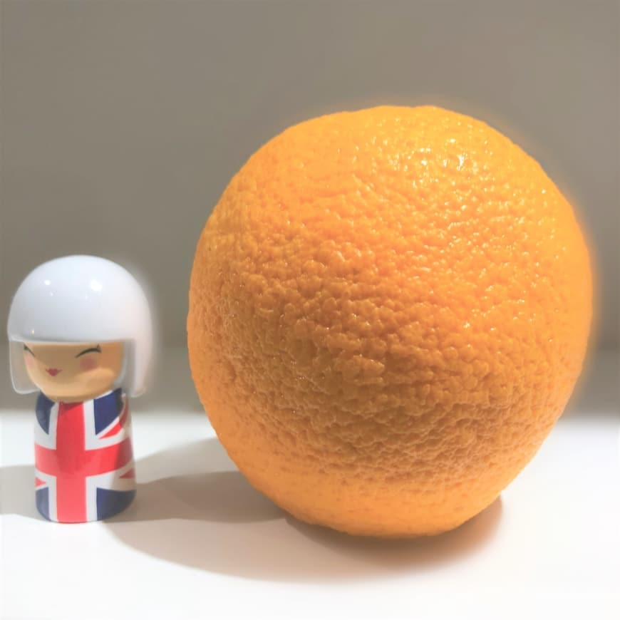 Bild på kokeshi och en apelsin