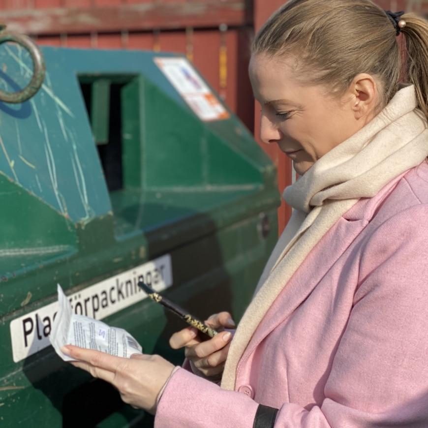 Yasemin scannar produkt framför återvinningen