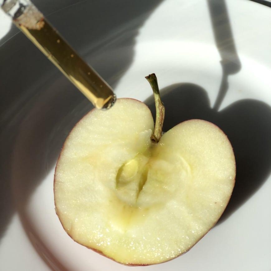 Bild på äppelhalva som får C-vitamindroppar