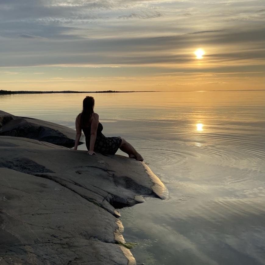 Yasemin sitter på klippor vid havet